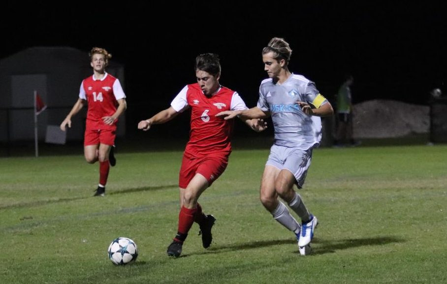 Senior Parker Wickizer defends the ball against East River. The team won the game 2-1.