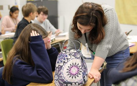 Advanced Placement Human Geography teacher helps student with her classwork.