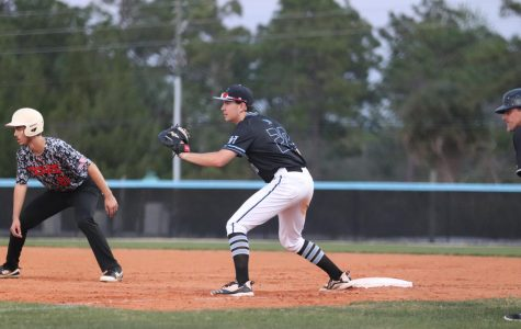 Ryan Carroll holds the runner close to first in the Tuesday game against Winter Springs.