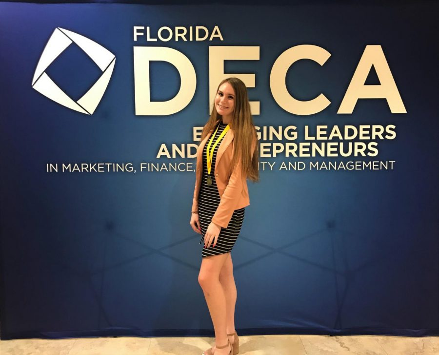 Junior and DECA president Laura Darty poses for a picture after receiving a first place medal for presentation in her category.