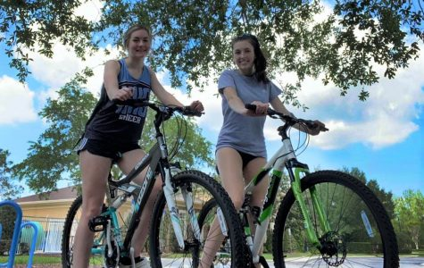 Junior Madison Drewry and her younger sister Macy take an afternoon bike ride together on April 9 around the Live Oak Reserve.