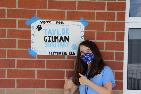 Taylor Gilman hanging campaign posters to encourage this year's seniors to vote for her.