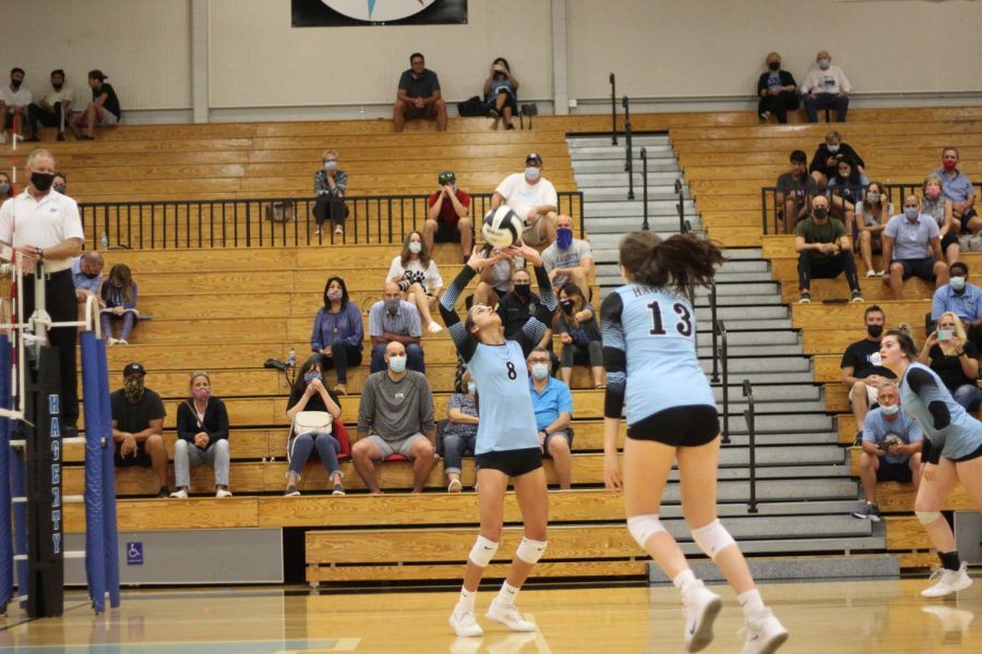 Freshmen Sophia Marini sets senior Madison Drewry up the middle against University. They would go on to capture their sixth consecutive district championship.