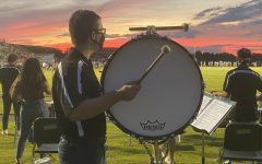 Percussionist Matt Hurley plays bass drum at a Friday night football game. Many band students are excited to participate in pep band.