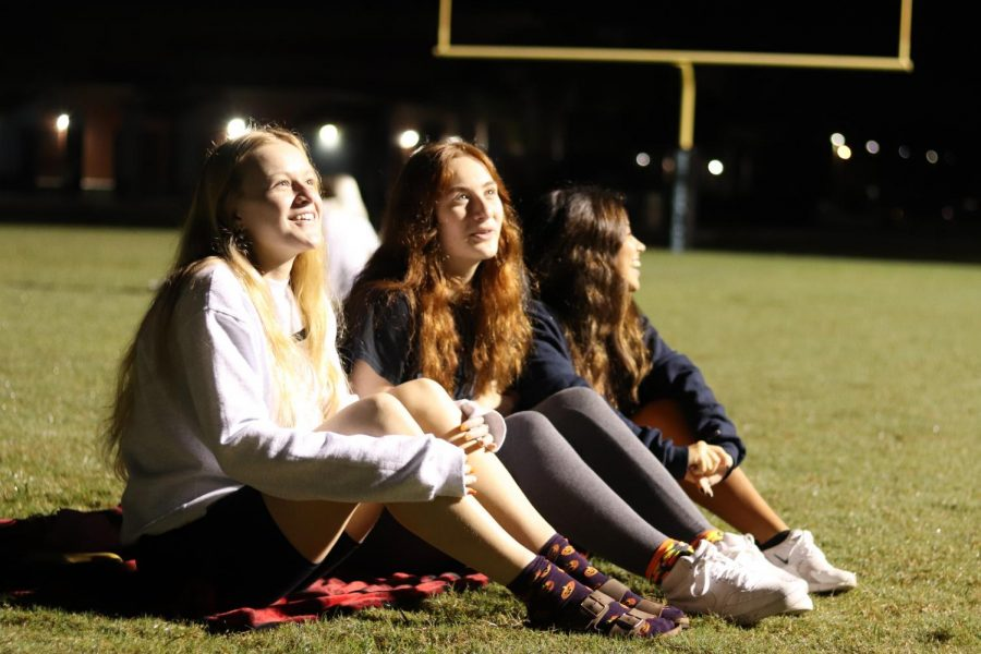 Seniors Faith Hammock, Julia Johnson and Skyler Diserafino wait for the sunrise. They all met up together on the football field with other seniors.