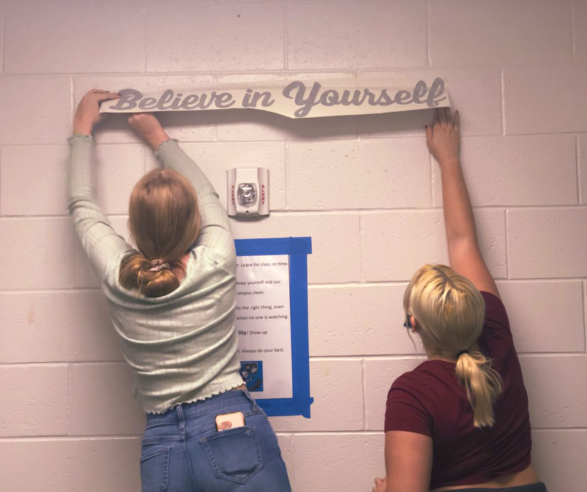 Freshmen+Margaret+Neely+and+Katie+Pollack+are+student+volunteers+on+the+committee.+They+hang+up+vinyl+signs+with+positive+affirmations.