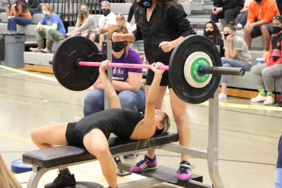 Senior Megan Carlson completes a bench press at the district championship. The girls' weightlifting team came in first place with 77 points.