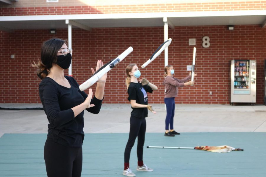 Working on their rifle toss on a Thursday afternoon practice, junior Hannah Makhecha, senior Kayden Howell and junior Brooke Karten practice the rifle routine.