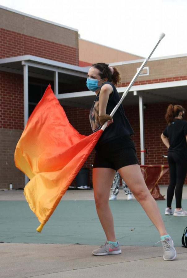 One of the few seniors on the team, Hannah Sanchez leads the winter guard during the flag routine, practiced immediately after the team ran around the courtyard.