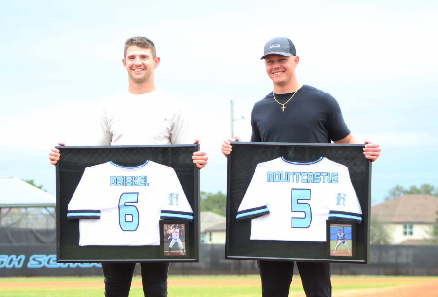Broncos quarterback Jeff Driskel (left) and Orioles third baseman Ryan Mountcastle (right) accept their retired jerseys at home plate.