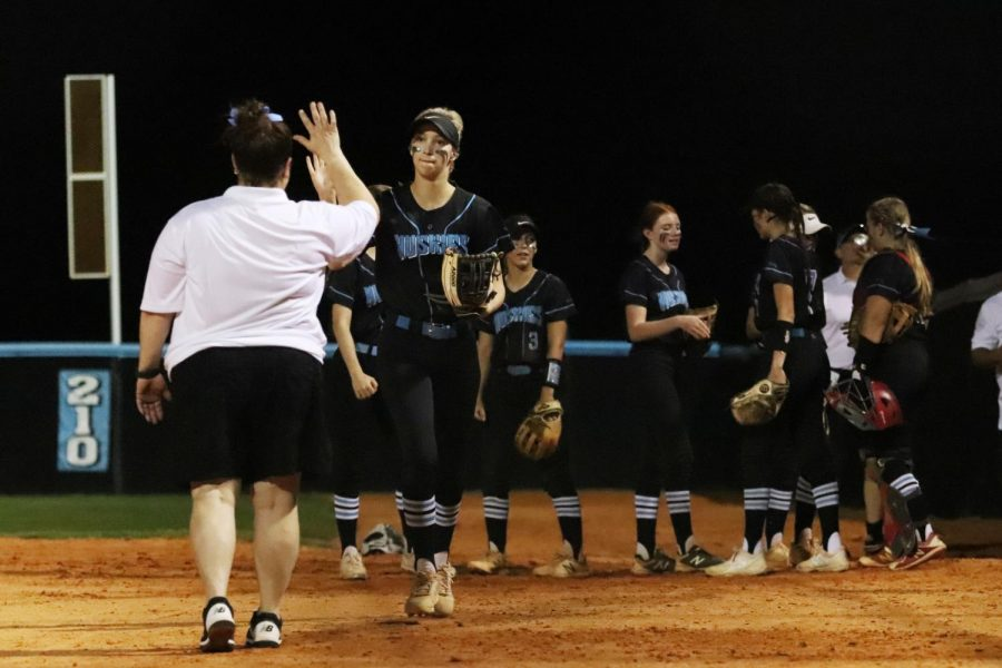 Senior Lauren Tulp high fives girls softball coach Wendy Acey in celebration.