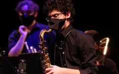 Junior Victor Acuna plays the saxophone during a virtual concert. Students have coverings over their instruments and wear special masks when playing them.