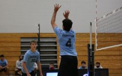 setter Brian Camacho is setting the ball to middle hitter Caden Douglass.