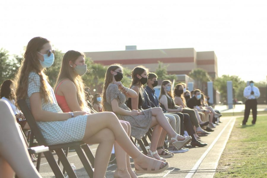 Students sit along the track at the Sam Momary Stadium, waiting to be called up onto the stage. Chairs were socially distanced and all attendants wore masks.