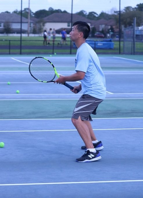 Senior Nicolas Cai prepares with the rest of his team for a match. In his doubles matches he was 7-4 and singles he was 4-7.