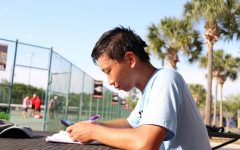 Senior Nicolas Cai works on his homework at tennis practice. Being in the gifted program often required setting aside a lot of time for assignments.