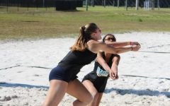 Junior Hope Lusher dives in front of junior teammate Lauren Andres to dig a returning ball.