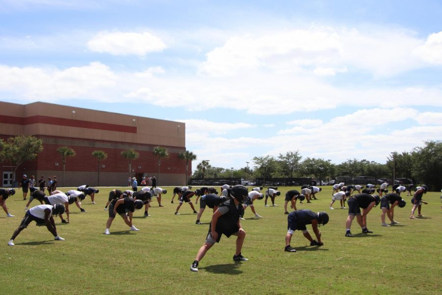 The varsity football team is stretching before their practice.