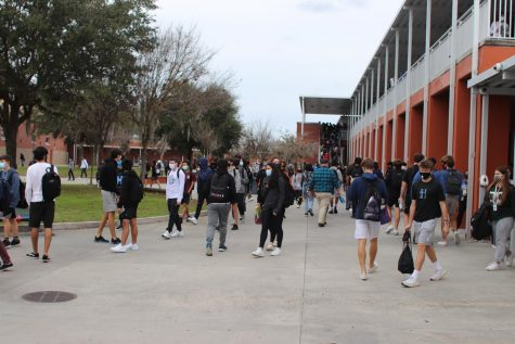 Students are walking to their next class, and they are following mask protocols.
