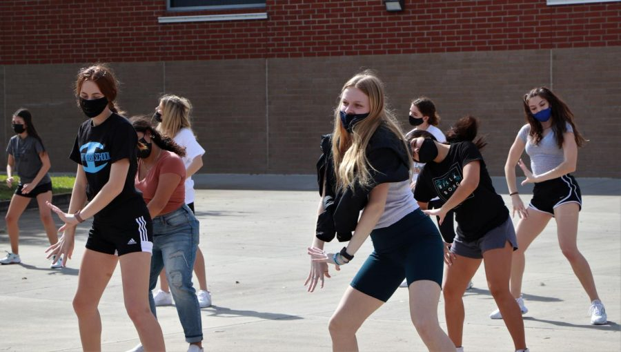 The dance team practices outside in the courtyard, preparing for their show in May. Practicing in the courtyard like this will be apart of their summer routine.