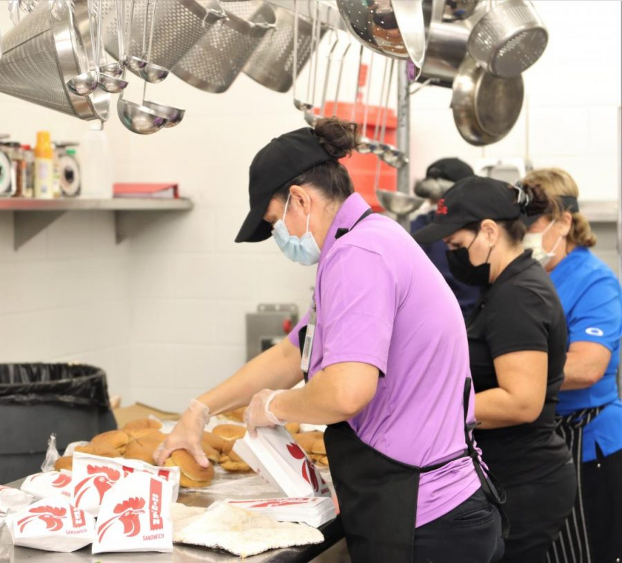 Cafeteria staff prepare chicken sandwiches for lunch. The staff prepare food three times a day for each meal opportunity on campus.