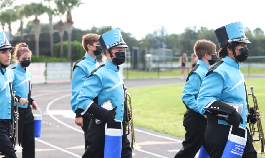 Sophomore Sophia Garbelman walks with the band to the stands before the game. The band walked together to the stands in uniform, including matching masks and water bottles.