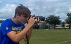 Taking pictures at football practice after school, senior James Hilston works as the team photographer.