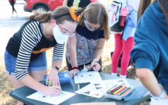 Sophomore Madalynn Flynn colors a Halloween picture with her buddy. Buddies spent their time coloring, playing games and trick or treating during the event.