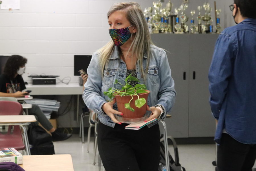 Julie Durgin carries a plant that was a gift from one of her students. This plant was given to her the Friday she left, during a Debate party that was organized.